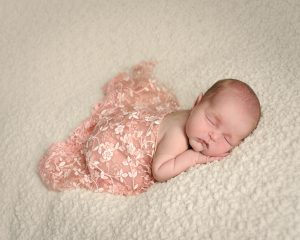 newborn baby photograph with pink lacy throw