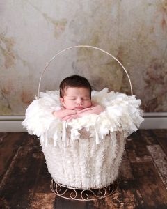 Newborn babt in basket leaning on hands by Treasured Moments Photography Limited